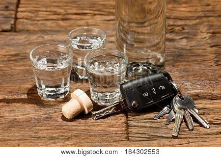 Shot glasses and a car key on an old wooden table. Don't drink and drive.