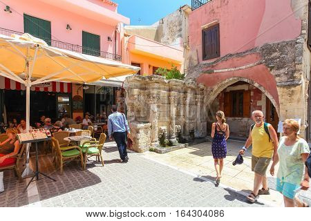 Rethymnon, Island Crete, Greece - July 1 2016: People are eating in cafe located near the Rimondi Fountain in Rethymnon (part of Old Town). The Rimondi fountain was built in 1626 by the city's Rector A. Rimondi.