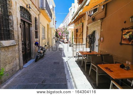 Rethymnon, Island Crete, Greece - July 1 2016: The narrow street of Rethymnon (part of Old Town) where there are a lot of small cafes and shops