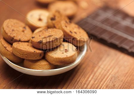 Beautiful tasty biscuit cookies with chocolate chips standing in plate on wooden table with crumbs and chocolate bar at the background. Shallow dof. Focus on foreground.