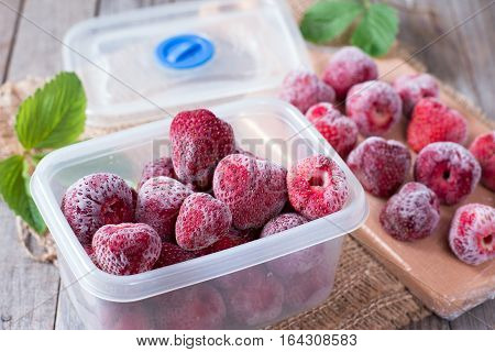 Frozen strawberries in box on a wooden background