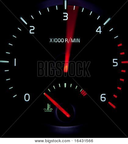Acceleration - close-up view of a revolution counter tachometer while speeding up in a modern car