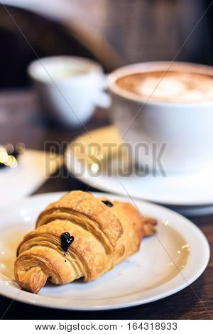 Delicious croissant and coffee. Breakfast with Coffee cup and fresh baked croissants on wooden background. Vintage effect style pictures. Selective focus. Shallow depth of field.