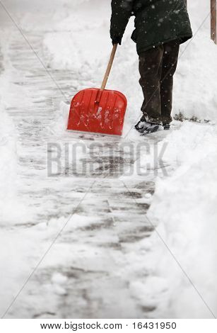 Man shoveling snow from the sidewalk in front of his house after a calamitous snowfall in a city