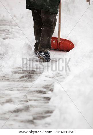 Hombre de la pala de nieve de la acera frente a su casa después de una fuerte Nevada en una ciudad