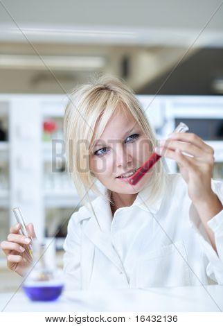 Closeup of a female researcher holding test tubes and carrying out research experiments in a chemistry lab