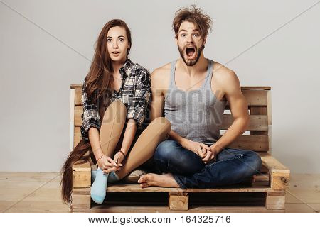 Young Couple On Wooden Sofa