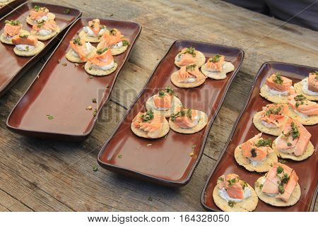 Four platters with fresh crackers topped with grilled salmon and mustard sauce offered to guests at party.