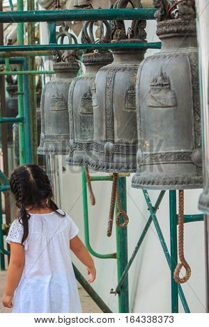Girl white shirt with row of bells in buddhist temple in Thailand. Buddhist temple bells. Bells of the old temple in Thailand