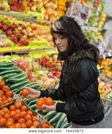 Beautiful young woman buying fruits and vegetables at a supermarket/grocery