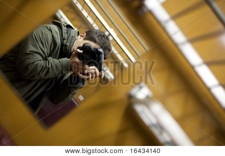 young man on a train taking a self portrait with the able assistance of a mirror