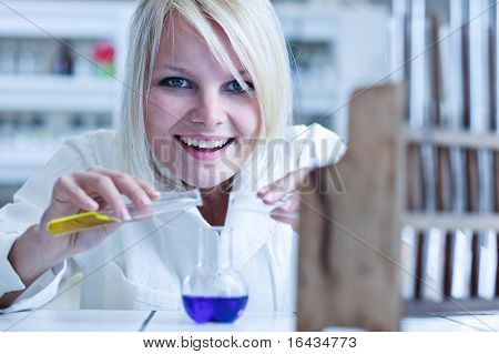 Closeup of a female researcher carrying out experiments in a laboratory (color toned image)