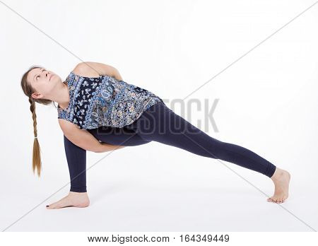 Attractive happy young woman working out indoors. Portrait of beautiful model doing exercises. Parivrtta Parsvakonasana. Full length
