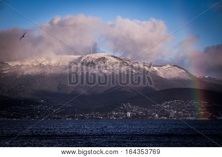 Morning view of Hobart, Tasmania, Australia with a colorful rainbow and Mt. Wellington covered in snow in the background