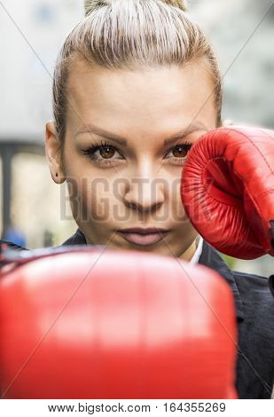 Business woman in red boxing gloves. She is fighter for success.