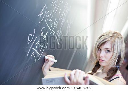 bastante joven estudiante escribiendo en la pizarra/pizarra durante una clase de matemáticas