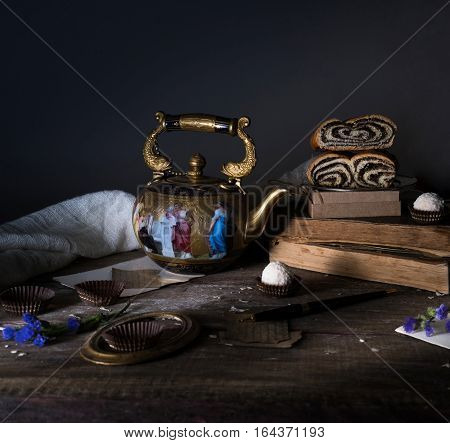 still life. vintage gold with enamel kettle, books, roll with poppy seeds on a wooden table. dark background.