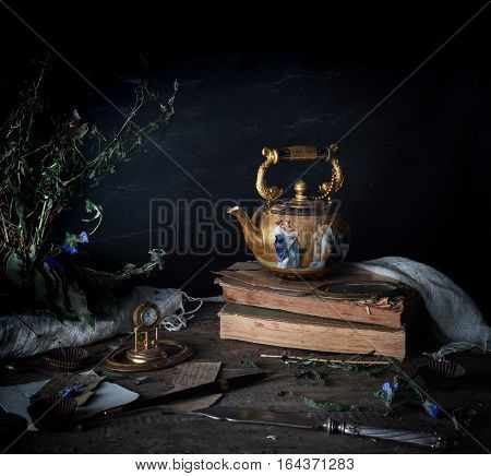 still life. vintage gold with enamel kettle, books and clock on the wooden table. dark background.