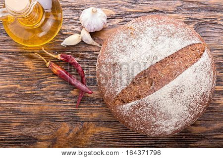 whole fresh loaf of round rye bread with a crispy crust standing beside olive oil garlic and chilli