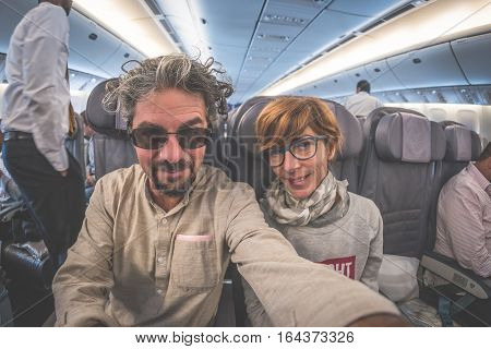 Cheerful adult caucasian couple taking selfie inside plane. Fish eye view from below. Concept of people traveling natural light.