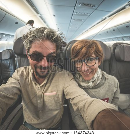 Cheerful Adult Caucasian Couple Taking Selfie Inside Plane. Fish Eye View From Below. Concept Of Peo