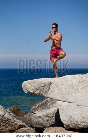 handsome young man meditating on a sunny rocky beach
