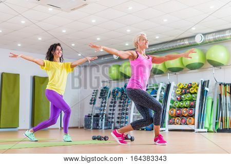 Two happy female fitness models dancing Zumba, doing aerobic exercises working out to lose weight in gym with colorful equipment in background.