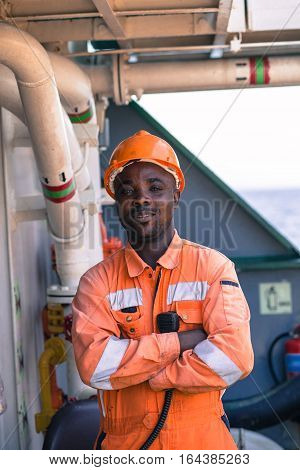 young african seaman standing on deck dressed in coverall and safety helmet with VHF radui station waiting for work orders