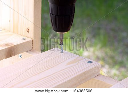 Making of wooden pallets. Tightening the screws with electric screwdriver. Photo closeup