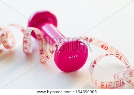 Pink fitness dumbbell with centimeter ribbon on bright shiny background. Sport or healthy life concept.