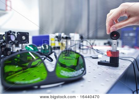 female scientist doing research in a quantum optics lab (color toned image)