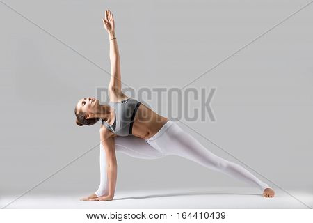 Young attractive woman practicing yoga, standing in Extended Side Angle exercise, Utthita parsvakonasana pose, working out wearing sportswear, indoor full length, isolated, grey studio background