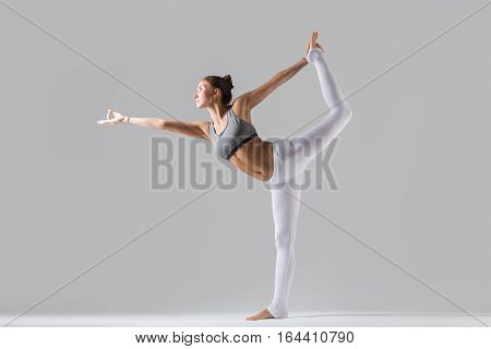 Young attractive woman practicing yoga, standing in Lord of the Dance exercise, Natarajasana pose, working out wearing sportswear, white pants, gray top, indoor full length, grey studio background