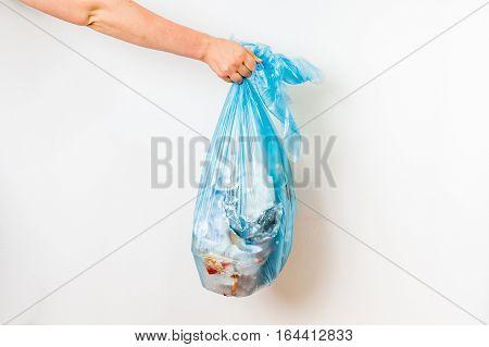 Female hand holding blue garbage bag isolated on white background