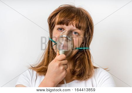 Diseased female patient with oxygen mask breathes oxygen in hospital