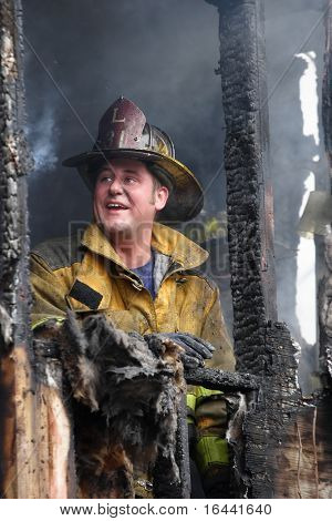 Firefighter looks up in relief after getting a house fire under control