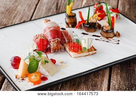 Delicatessen mix on white plate. Different gourmet snacks for wine or elegant event. Luxury lifestyle, expensive food, restaurant menu concept