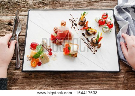 Tasting appetizer at restaurant flat lay, eater pov. Top view on white plate with delicatessen snacks mix and male hands holding cutlery, ready to it. Degustation, event organization concept