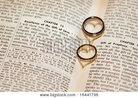 Two wedding rings on a bible, open to Corinthians Chapter 13,