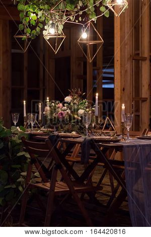 Decoration wedding table before a banquet in a wooden barn. Evening. Burning lights. Candles bouquet stemware.