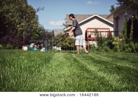 Teenage boy mowing lawn (extremely shallow depth of field, focus in foreground)