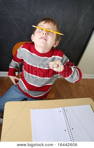 Bored student balancing a pencil on his nose