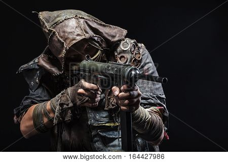 Nuclear post apocalypse life after doomsday concept. Grimy survivor with homemade weapons aiming a gun. Studio closeup portrait on black background