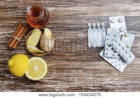 Ginger lemon honey and different drugs on wooden background.Alternative remedies and traditional pills to treat colds and flu. Natural medicine vs conventional medicine concept.