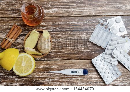 Ginger lemon honey and different drugs with thermometer on wooden background.Alternative remedies and traditional pills to treat colds and flu. Natural medicine vs conventional medicine concept.