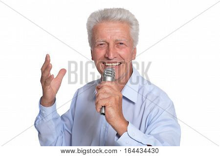 mature man with microphone posing against white background