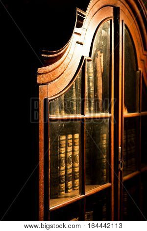 Vintage Russian wooden bookcase in the library. Collection of old books. Wooden book shelves with old library books. Vologda Russia.
