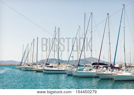 Sailing boats are moored in the harbor of Alghero Sardinia