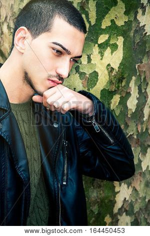 Portrait of thinking young man. A guy with a leather jacket with her hand near his chin and mouth is thinking. Near a tree trunk outdoors.