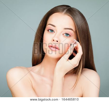 Spa Model Woman with Healthy Skin holding Ice Cubes. Young Perfect Woman on Gray Background